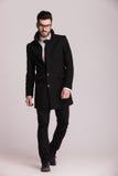 Hübscher junger Geschäftsmann, der einen langen schwarzen Mantel trägt Lizenzfreies Stockfoto