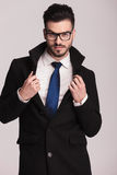 Hübscher junger Geschäftsmann, der seinen Kragen zieht Stockbild