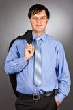 Hübscher junger Geschäftsmann, der seins Anzugsjacke auf seinem shoul hält Lizenzfreie Stockfotografie