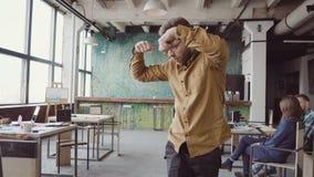 Hübscher junger Geschäftsmann, der Siegtanz über erfolgreiche Leistung tut Glücklicher Mann im modernen modischen Büro stock footage