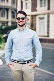 Hübscher junger Geschäftsmann in der Sonnenbrille gehend auf Straße Er hält Hände in den Taschen und lächelt zur Kamera lizenzfreies stockbild