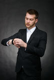 Hübscher junger Geschäftsmann, der Uhr betrachtet Stockfoto