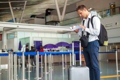 Hübscher junger Geschäftsmann im weißen Hemd, das heraus seine Karte ausdehnt, bei der Stellung vor der Fluglinie überprüfen im Z lizenzfreie stockbilder