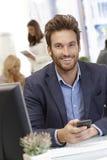 Hübscher junger Geschäftsmann mit Mobiltelefon Stockfoto