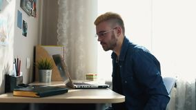 Hübscher junger Hauptfreiberufler mit den Gläsern und gelbem Haar, die zu Hause, unter Verwendung eines Laptops arbeiten Während  stock footage