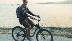 Hübscher junger Hippie-Mann fährt entlang das Ufer gegen den Hintergrund des Sonnenuntergang-Ferien-Feiertags-Tätigkeits-Konzepte Lizenzfreie Stockfotografie