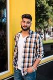 Hübscher junger indischer Mann, der an der Straße aufwirft lizenzfreie stockbilder
