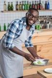 Hübscher junger Kellner, der schmutzige Teller nimmt und positiv schaut stockfoto