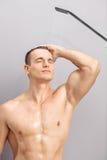 Hübscher junger Kerl, der eine Dusche nimmt Stockfotos