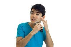 Hübscher junger Kerl mit dem schwarzen Haar rasiert seinen Bart und blickt in Richtung lokalisiert auf einem weißen Hintergrund Stockfotos