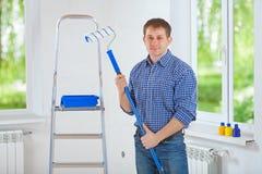 Hübscher junger lächelnder Maler, der das paintroller betrachtet Ca hält lizenzfreies stockfoto