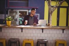 Hübscher junger männlicher Fachmann, der Laptop an der Kaffeestube verwendet lizenzfreies stockfoto