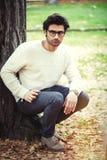 Hübscher junger Mann allein in der Natur nahe einem Baum draußen Lizenzfreie Stockfotos
