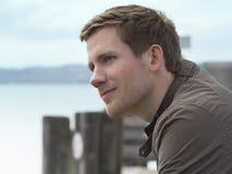 Hübscher junger Mann auf einem Küstenpier Stockfotos