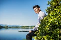 Hübscher junger Mann auf einem See in einem sonnigen, ruhig stockbilder