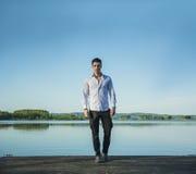 Hübscher junger Mann auf einem See in einem sonnigen, ruhig lizenzfreies stockbild