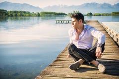 Hübscher junger Mann auf einem See in einem sonnigen, ruhig lizenzfreie stockfotografie