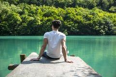 Hübscher junger Mann auf einem See in einem sonnigen, ruhig stockfotos