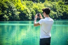 Hübscher junger Mann auf einem See in einem sonnigen, ruhig lizenzfreies stockfoto