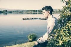 Hübscher junger Mann auf einem See in sonnigem, ruhig lizenzfreies stockfoto