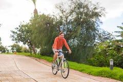 Hübscher junger Mann auf Fahrrad im Park Fahrrad, Freizeit und Leutekonzept Stockfotos