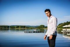 Hübscher junger Mann auf See in einem sonnigen, ruhig lizenzfreies stockfoto