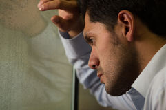 Hübscher junger Mann depresed, grauer Hintergrund Stockfoto