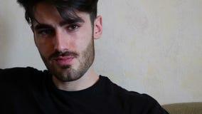 Hübscher junger Mann, der auf Couch sitzt stock video footage