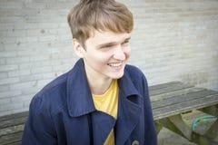 Hübscher junger Mann, der auf einem Banklächeln sitzt offen lizenzfreies stockbild