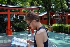 Hübscher junger Mann, der auf Kyoto reist und zu seiner Karte der Stadt schaut Lizenzfreie Stockfotos