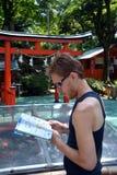 Hübscher junger Mann, der auf Kyoto reist und zu seiner Karte der Stadt schaut Stockbild