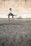 Hübscher junger Mann, der auf Marmorbank mit Ziegelsteinhintergrund sitzt Stockfoto