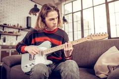 Hübscher junger Mann, der auf Sofa und verfassender Melodie sitzt stockfoto