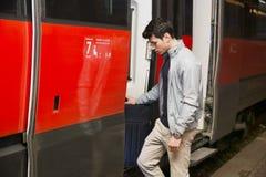 Hübscher junger Mann, der an Bord in Zug einsteigt lizenzfreies stockfoto