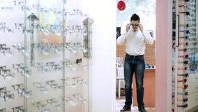 Hübscher junger Mann, der Brillen im optischen Speicher wählt Optik, Einzelhandelsgeschäft des Optikers Gesundheitswesen, Sehverm stock footage