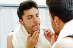 Hübscher junger Mann, der das Spitzenschauen des schwarzen Unterhemds im Spiegel, unter Verwendung der kleinen Scheren trimmen Ba Lizenzfreie Stockfotografie