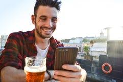 Hübscher junger Mann, der das Telefon betrachtend lächelt und ein Bier in einer Bar draußen trinkend stockbild