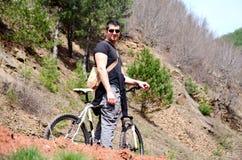 Hübscher junger Mann, der in den Berg radfährt lizenzfreie stockbilder