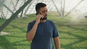 Hübscher junger Mann, der den Kopf spricht auf Smartphone ablehnt und rüttelt stock video footage