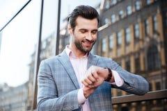 Hübscher junger Mann, der die Zeit auf seiner Armbanduhr überprüft Stockbilder