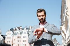 Hübscher junger Mann, der die Zeit auf seiner Armbanduhr überprüft Lizenzfreie Stockfotografie