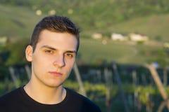 Hübscher junger Mann, der draußen in den Sonnenuntergang mit einem träumerischen nachdenklichen Ausdruck, einem Haupt- und Schult stockfotografie