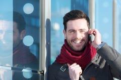 Hübscher junger Mann, der draußen durch Handy lächelt und nennt Stockfoto