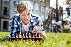 Hübscher junger Mann, der draußen Schach spielt Stockfoto
