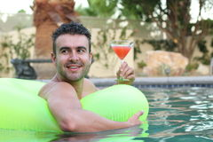 Hübscher junger Mann, der ein Cocktail bei der Entspannung in einem Swimmingpool trinkt Stockfoto