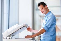 Hübscher junger Mann, der eine Exemplarmaschine verwendet Stockbild