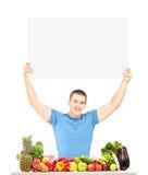 Hübscher junger Mann, der eine Leerplatte hält und mit Lebensmittel aufwirft Lizenzfreies Stockbild