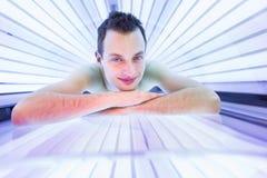 Hübscher junger Mann, der in einem modernen Solarium sich entspannt Lizenzfreies Stockfoto