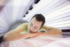 Hübscher junger Mann, der in einem Solarium sich entspannt Stockbild