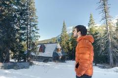 Hübscher junger Mann, der erstaunliche Ansicht in Tal mit Gebirgshütte und Nadelbaumwald betrachtet stockbilder